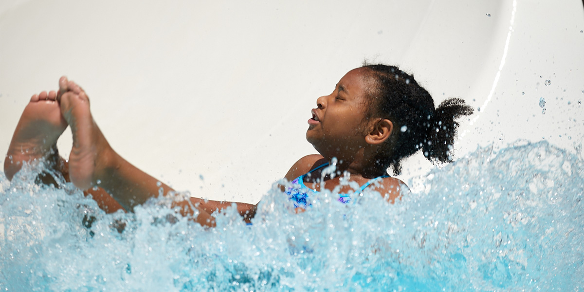 young African American girl landing in pool at the bottom of the water slide