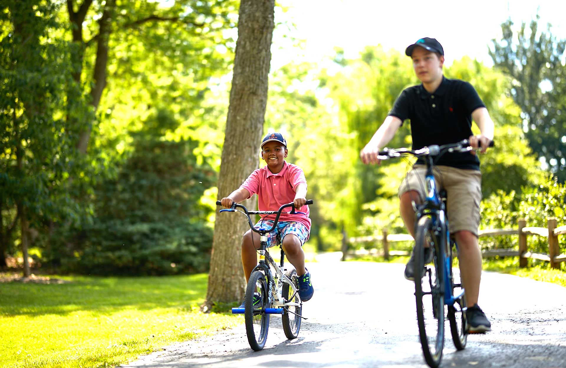 young African American and teenage white boy riding bikes together on bike path